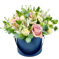 Composition of white alstroemeria and roses in a hat box.